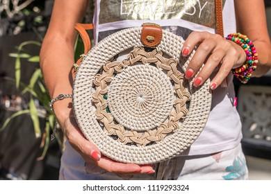 Woman hands with fashionable stylish white rattan bag. Tropical island of Bali, Indonesia. Rattan handbag.