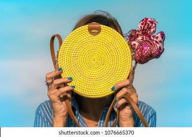 Woman hands with fashionable stylish yellow rattan bag and silk scarf outside. Tropical island of Bali, Indonesia. Rattan handbag and silk scarf.