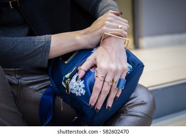 woman hands with fau bijou on blue bag
