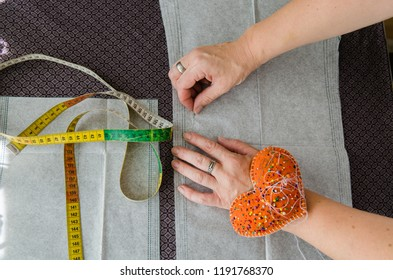 Woman hands fix a pattern to the fabric before cutting it for sewing