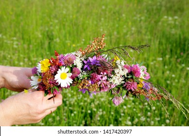 Woman hands in flower meadow preparing flower crown, close up