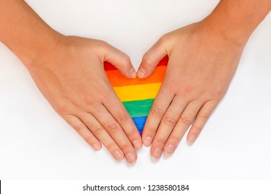 woman hands forming heart painted like LGBT flag on white background, symbol gay, lesbian, bisexual, transgender love. Lgbtq rights concept