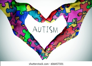 woman hands forming a heart patterned with many puzzle pieces of different colors, symbol of the autism awareness, and the text autism, with a slight vignette added