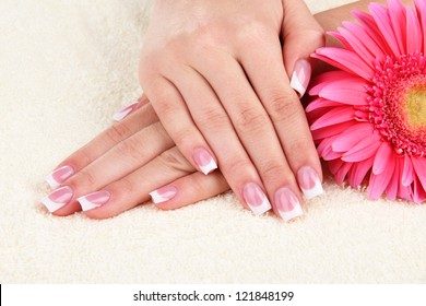 Woman hands with french manicure and flower on towel
