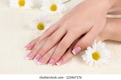 Woman hands with french manicure and flowers on towel