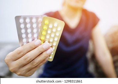 Woman hands give birth control pills in hand. Taking Contraceptive Pill. Medicine drug and health concept. soft focus. Leave copy space empty for text writing.