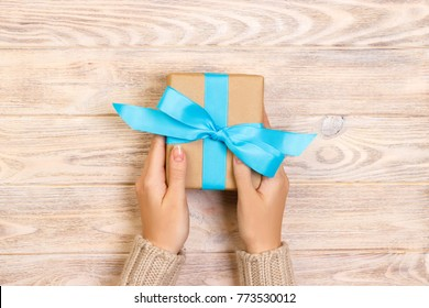 Woman hands give wrapped valentine or other holiday handmade present in paper with blue ribbon. Present box, decoration of gift on white wooden table, top view with copy space.