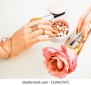 woman hands with golden manicure and many rings holding brushes,
