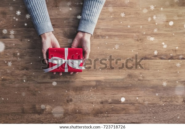 Woman hands in gray sweater, on wood table background,giving red Christmas holiday gift boxes top view with copy space and falling snow effect
