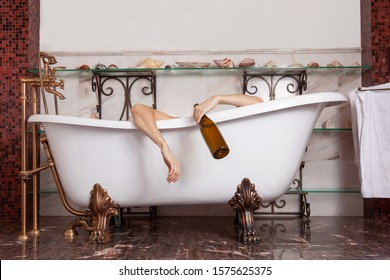Woman hands hanging from the bathtube, with epmty wine bottle. Drunk, depression, loneliness concept. Luxury classic antique interior of bathroom.