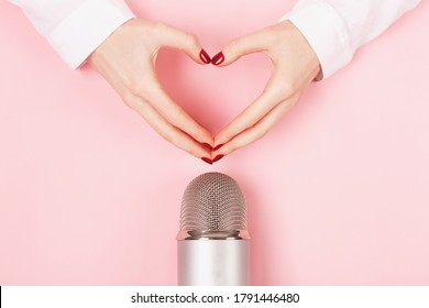 Woman hands in a heart shape and a microphone on pink background.