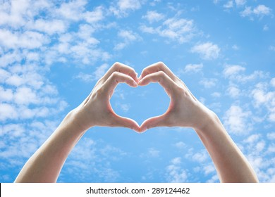 Woman hands in heart shape raising against blue sky with clouds