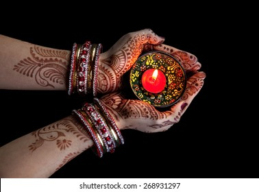 Woman hands with henna holding candle isolated on black background