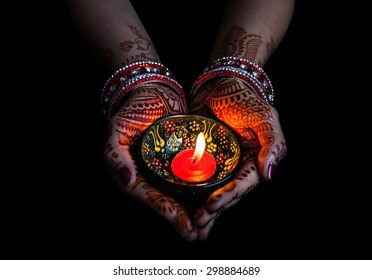 Woman hands with henna holding lit candle isolated on black background with clipping path