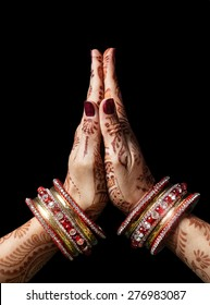 Woman hands with henna in Namaste mudra on black background