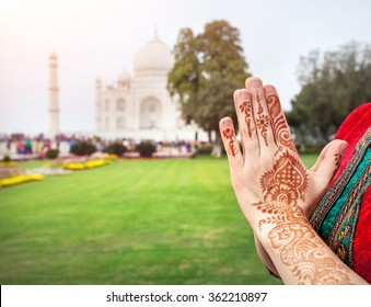 Woman hands with henna painting in Namaste gesture near Taj Mahal in Agra, Uttar Pradesh, India
