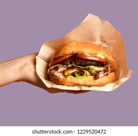 Woman hands hold big cheese burger barbeque sandwich with marble beef on orange background