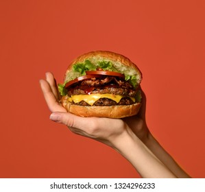 Woman hands hold big double cheeseburger barbeque sandwich with marble beef on orange red background