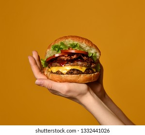 Woman hands hold big double cheeseburger burger sandwich with beef and bacon on yellow background