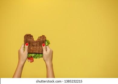 woman hands hold bitten sandwich on yellow background. Sandwich promotion concept.