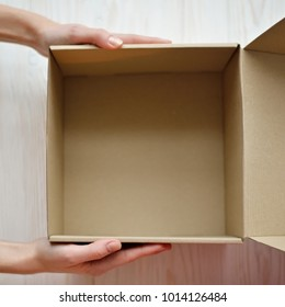 Woman hands hold an empty (blank) gift box (container, case) for holiday, christmas, thanks giving day, birthday top view.