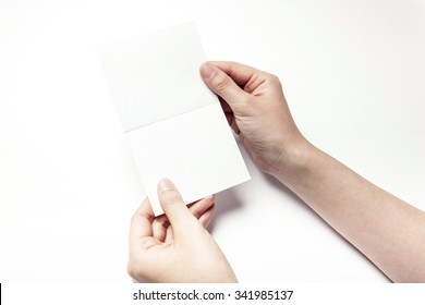 A woman hands hold a empty(blank, vacant, hollow) white paper for thank you card, letter,  postcard top view isolated white at the studio.
