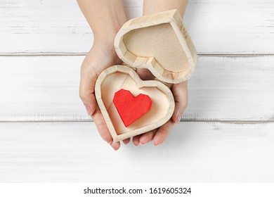 Woman Hands Hold Paper Red Heart inside Heart Box on white wood background. Success Love Concept with copy space.