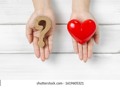 Woman Hands Hold Question Mark and Red Heart on white wood background. Solving Problem of Love Concept.