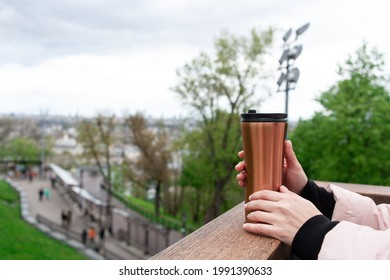 Woman hands hold thermo cup on cold weather street. Bronze color thermo mug stands on the nature against city view. Close up