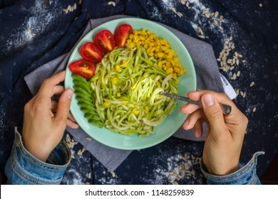 Woman hands hold and twirl zucchini raw vegan pasta with fork. Vegan spaghetti with avocado dip sauce on plate. Vegetarian healthy lunch or vegetables dinner.  Top above view