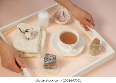 Woman hands hold white wooden tray with bath accessories,  beauty, spa concept, handmade soap, rose and clay cleansing face  mask, top view, cup of tea, pink background, creative flat lay.