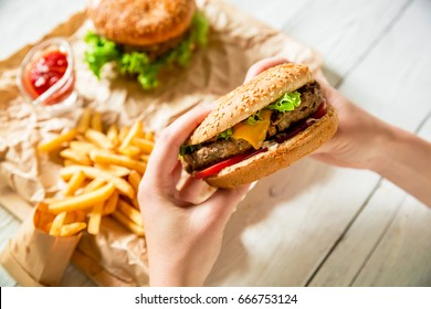 Woman hands holding american tasty burger and french fries, sauce on the wooden plate, white table. Flat lay. Top view