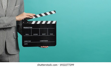 Woman hands holding black Clapperboard or film slate and wear grey suit. it use in videography ,movies and cinema industry on green or Tiffany Blue background.Clapper board for director.