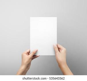 Weibliche Hände, die ein leeres Blatt A5 oder ein Buchstabenpapier auf grauem Hintergrund halten.
