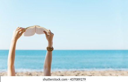 Woman hands holding book with the sea side in background.