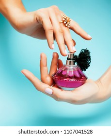 woman hands holding bottle of perfume pink manicure and jewelry