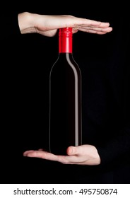 Woman hands holding bottle of red wine on black background