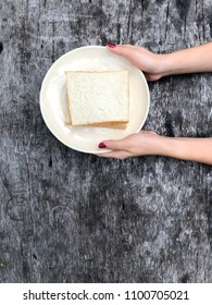 Woman hands holding bread in the morning on vacation summer time, close up. Girl having breakfast on holiday, Top view.
