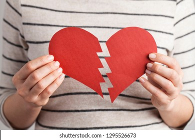 Woman hands holding a broken heart