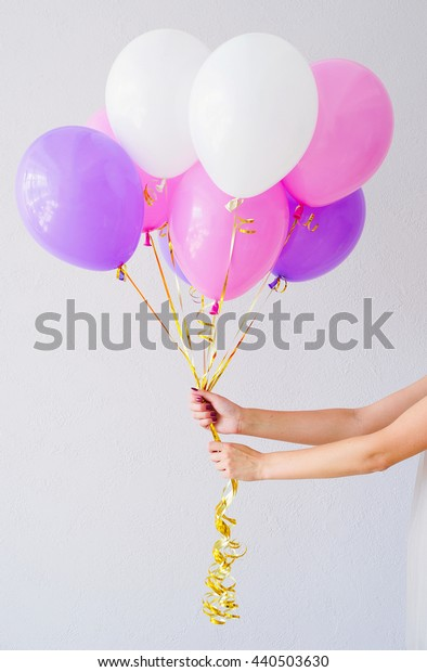 Woman hands holding bunch of colorful balloons