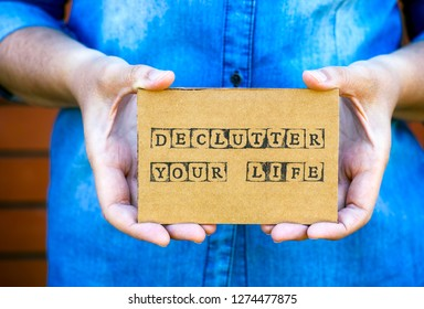 Woman hands holding cardboard card with words Declutter Your Life made by black alphabet stamps.