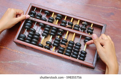 Woman hands holding Chinese ABACUS old antique calculator retro finance education ,tool work business accounting