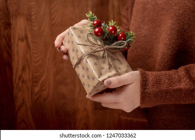 Woman hands holding Christmas handmade gift box decorated with mistletoe