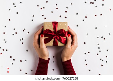 Woman hands holding christmas holiday gift box on decorated festive table with sparkle stars on white background. Packaging gift wrap