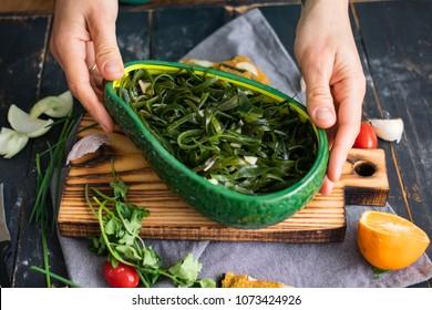 Woman hands holding chuka seaweed salad in bowl. Asian Japanese traditional food with laminaria, wakame, kelp. Raw vegan vegetarian healthy food