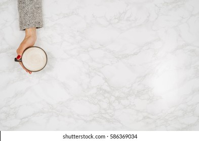 Woman hands holding coffee mug or cup on colorful table. Photograph taken from above, top view with copy space
