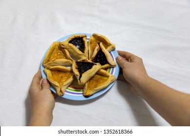 woman hands holding a colored plate with Hamantash Purim Blueberry and apricot jam cookies on white tablecloth