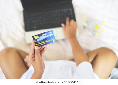 Woman hands holding credit card and using laptop for online shopping with shopping cart on the bed / people paying technology money wallet online payment at home , Credit card mockup