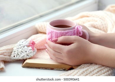 Woman hands holding cup of coffee near the window
