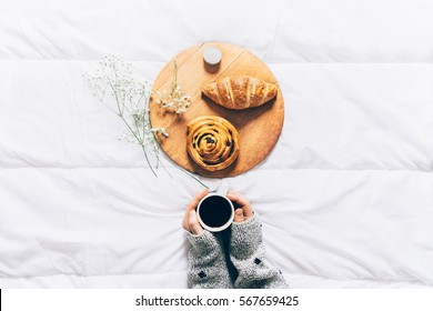Woman hands holding cup of coffee in bed. Top view of breakfast in bed